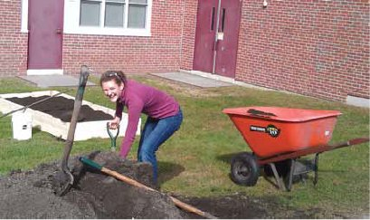SSF member Nell Houde shovels compost into raised garden beds she helped build at Lebanon High School.