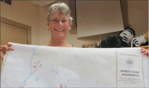 Lebanon Energy Advisory Committee chair Barbara Hirai holds a map showing the streetlights in Lebanon.