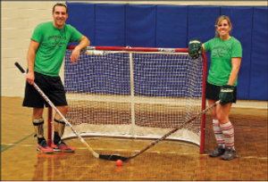 Co-founders of the Upper Valley Floor Hockey Association Jared and Becky Rhoads; Ben Arellano works out as the goalie for the Red Team; Shawn Quelch and Becky Rhoads square off to start the game.