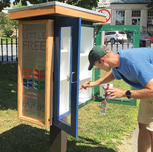 Zachary Brock touches up the Little Free Library in Colburn Park