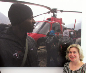 Dr. Devon Davis poses with a life-size poster of a Global Rescue mission